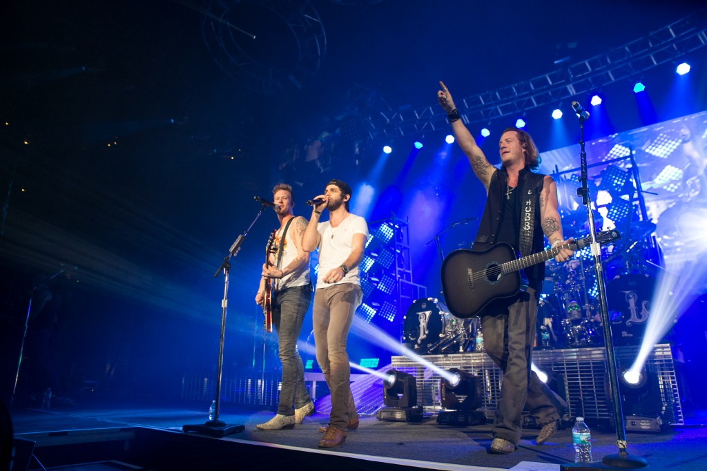 Country star Thomas Rhett joins Florida Georgia Line onstage at the inaugural AAA Insurance Monumental Music Jam concert Hank FM produced in February 2014