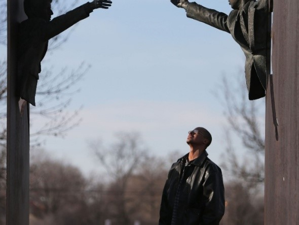 Joseph Reese of Indianapolis looks up at a statue depicting Martin Luther King Jr. and Robert F. Kennedy at MLK Park at 17th & Broadway. ROBERT SCHEER/THE STAR